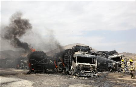 Afghan firefighters spray water on burning NATO supply trucks in Samangan province, July 18, 2012. A bomb planted by the Taliban destroyed 22 NATO trucks carrying supplies to their forces in northern Afghanistan, the Taliban and police said on Wednesday. REUTERS/Stringer