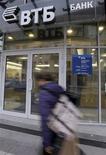 Женщина проходит мимо отделения банка в Санкт-Петербурге, 16 сентября 2008 года. Второй по величине банк РФ ВТБ рассчитывает в течение ближайших месяцев договориться с компанией Металлоинвест, управляющей стальными и железорудными активами российского миллиардера Алишера Усманова, о продаже ей 20-процентного пакета холдинга, доставшихся госбанку в конце прошлого года. REUTERS/Alexander Demianchuk