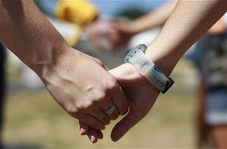 Volunteers hold hands before assembling the AIDS Memorial Quilt to mark the 25th anniversary of The AIDS Memorial Quilt and the 30 years since the HIV and AIDS epidemic was diagnosed in America, on the National Mall in Washington June 27, 2012. REUTERS/Kevin Lamarque