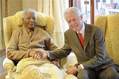 Former U.S. President Bill Clinton visits former South African President Nelson Mandela at his home in Qunu in South Africa's Eastern Cape province, in this handout picture taken July 17, 2012. Mandela celebrates his 94th birthday on July 18. REUTERS/Peter Morey/Photographic/Handout
