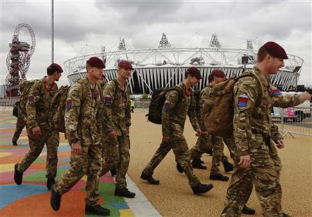 Soldiers pass the Olympic Stadium in the London 2012 Olympic Park in Stratford, east London July 17, 2012. REUTERS/Luke MacGregor