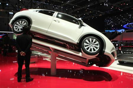 A visitor looks under a Honda Civic model displayed on the car maker's booth during the first media day of the Geneva Auto Show at the Palexpo in Geneva, March 6, 2012. REUTERS/Denis Balibouse