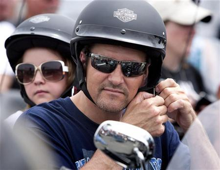 Todd Palin, husband of Sarah Palin, former governor of Alaska, adjusts his helmet as his daughter Piper sits behind him before taking part in the Rolling Thunder motorcycle ride to honour U.S. veterans in Washington May 29, 2011. REUTERS/Joshua Roberts