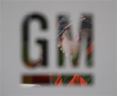 A worker walks behind a logo of General Motors after the announcement of the closing of the Opel assembly plant in Antwerp January 21, 2010. REUTERS/Francois Lenoir