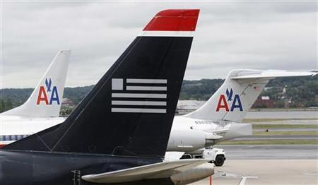 A US Airways plane and American Airlines planes share a terminal at Ronald Reagan National Airport in Washington April 23, 2012. REUTERS/Kevin Lamarque