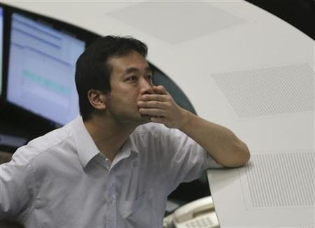 A Tokyo Stock Exchange employee looks up at a monitor displaying market indices at the bourse in Tokyo July 13, 2012. REUTERS/Toru Hanai