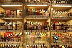 Бутылки с алкогольными напитками стоят на полке магазина в Шанхае, 9 марта 2011 года. Один из крупнейших производителей водки в России - Синергия увеличила фактические отгрузки алкогольной продукции в преддверии повышения акцизов с 1 июля, которое может вылиться в существенное замедление продаж в третьем квартале. REUTERS/Aly Song