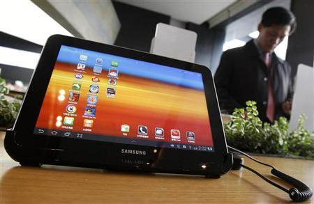 A visitor looks around behind Samsung Electronics' Galaxy Tab 10.1 tablet displayed for customers at a registration desk at South Korean mobile carrier KT's headquarters in Seoul December 9, 2011. REUTERS/Kim Hong-Ji