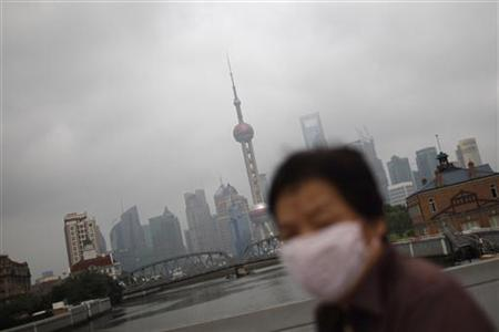 A woman wearing a mask walks at the Bund along the Huangpu River on a hazy day in Shanghai in this June 11, 2012 file photo. REUTERS/Aly Song/Files
