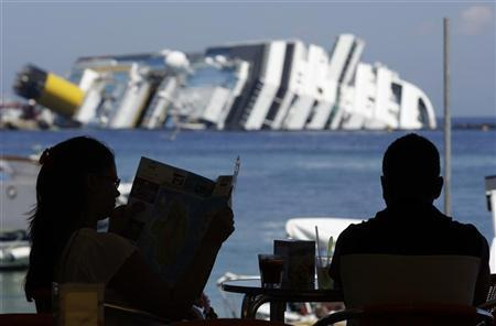 Vacationers sit and read close to the wreckage of capsized cruise liner Costa Concordia near the harbour of Giglio Porto July 12, 2012. REUTERS/Remo Casilli