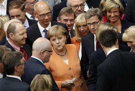 German Chancellor Angela Merkel (C) and her fellow parliamentarians line up to vote on a Spanish bank aid package in the Bundestag, the lower house of parliament in Berlin, July 19, 2012. REUTERS/Thomas Peter