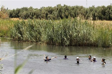 Youths bathe in a stream at the Valley of Springs near the Jordan River July 16, 2012. The Biblical river, which has inspired countless spirituals and folk songs, is just a narrow stream in many parts - polluted and stagnant. But that's about to change. Thanks to desalination and wastewater recycling, there is more fresh water to go around and the Jordan will slowly be returned to its former glory. Picture taken July 16, 2012. REUTERS/Baz Ratner