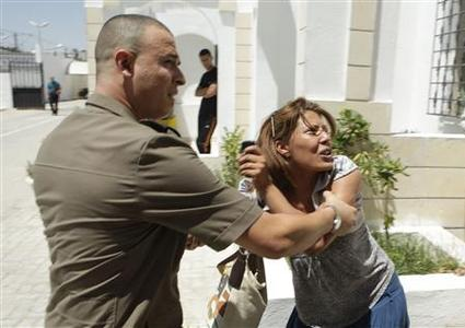A police officer restrains a relative of a convicted official as the police break up a fight between relatives of protesters who died during the January 11 revolution and relatives of those convicted after the verdict for officials involved in the deaths was pronounced in Tunis July 19, 2012. A Tunisian military court sentenced ousted president Zine al-Abidine Ben Ali's interior minister and 38 other security officials to up to 20 years jail on Thursday over the deaths of the protesters during the revolution that launched the Arab Spring. REUTERS/Zoubeir Souissi