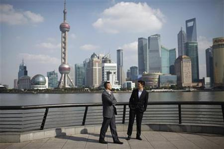 Businessmen walk on the Bund near the Huangpu River in front of the financial district of Pudong in Shanghai November 21, 2011. REUTERS/Aly Song