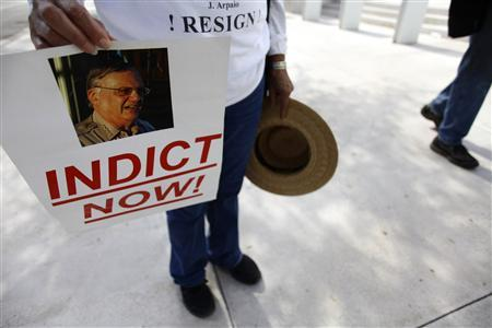 A protester holds a sign with a picture of Maricopa County Sheriff Joe Arpaio, during day one of Apraio's and his sheriff's department civil rights trial, outside the Sandra Day O'Connor United States Courthouse in Phoenix, Arizona July 19, 2012. REUTERS/Joshua Lott