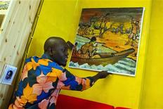 "Artist Christel Gbaguidi hangs up a painting at an exhibition at Afrika Haus (Africa House) in Berlin, July 18, 2012. Gbaguidi's painting is one of nearly 60 paintings now on display at Afrika-Haus (Africa House) in Berlin in an exhibition ""Migration and Me"" chronicling the grim experiences of African migrants who wash up in Europe in search of a better life. Picture taken July 18, 2012. REUTERS/Thomas Peter"