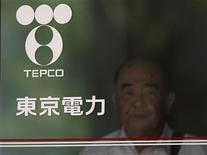 A man walking out is seen past Tokyo Electric Power Co (TEPCO)'s logo at the company headquarters in Tokyo July 19, 2012. REUTERS/Yuriko Nakao