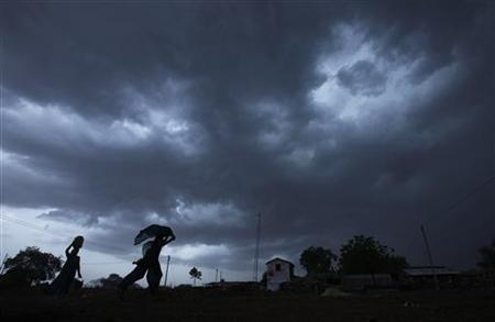 A girl runs for cover as it rains as monsoon clouds gather over Meerwada village in Guna district in Madhya Pradesh June 19, 2012. REUTERS/Adnan Abidi