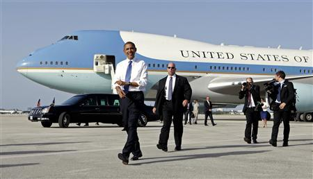 U.S. President Barack Obama rolls up his sleeves while walking from Air Force One upon his arrival in West Palm Beach, Florida July 19, 2012. REUTERS/Kevin Lamarque