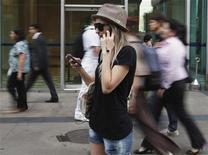 Mulher usa telefones celulares ao mesmo tempo para falar, ouvir música e enviar mensagens de texto no centro financeiro de São Paulo, em outubro de 2011. 26/10/2011 REUTERS/Nacho Doce