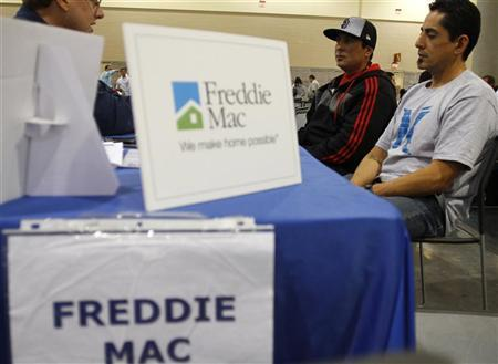 Home owners Jesse Fernandez (R) and his brother Joel Fernandez (C) speak with a Freddie Mac representative as they try to get a home loan modification during The Neighborhood Assistance Corporation of America event in Phoenix, Arizona, February 4, 2011. REUTERS/Joshua Lott