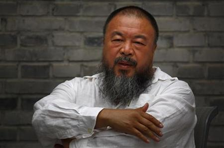 Chinese dissident artist Ai Weiwei folds his arms as he sits on a chair in the courtyard of his studio in Beijing June 20, 2012. REUTERS/David Gray/Files