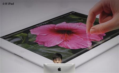 An employee sits in front of a poster advertising the New iPad at an Apple Store in Wuhan, Hubei province July 19, 2012. REUTERS/Stringer