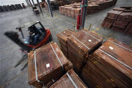 A worker loads copper cathodes into a warehouse near Yangshan Deep Water Port, south of Shanghai March 23, 2012. REUTERS/Carlos Barria