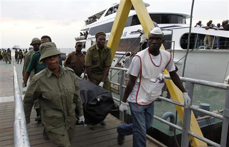 Volunteers carry a recovered body of a passenger who died during the ferry tragedy at the Port of Zanzibar, July 19, 2012. REUTERS/Thomas Mukoya