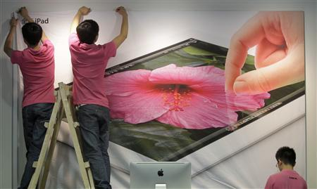 Employees hang a poster advertising the New iPad at an Apple Store in Wuhan, Hubei province July 19, 2012. REUTERS/Stringer
