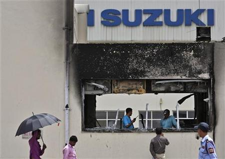A media personnel (bottom 2nd R) speaks with employees behind a damaged portion of Maruti Suzuki's plant in Manesar, located in Haryana, July 19, 2012. REUTERS/Ahmad Masood