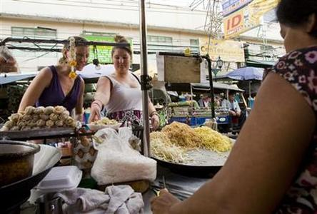Tourists select food from a street vendor on Khao San Road, a favourite tourist destination in the old section of Bangkok, May 18, 2010. REUTERS/Caren Firouz
