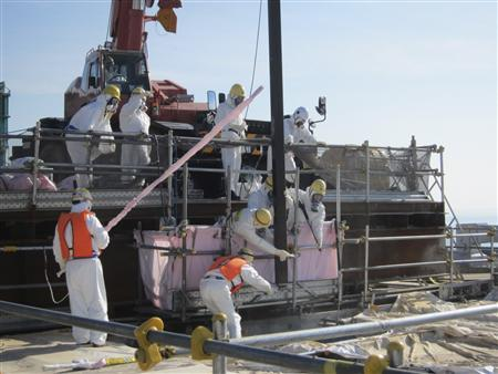 Workers wearing protective suits, work for removing unused nuclear fuel assemblies stored in the spent fuel pool of Tokyo Electric Power Co. (TEPCO)'s tsunami-crippled Fukushima Daiichi Nuclear Power Plant No. 4 reactor building in Fukushima prefecture, in this handout photo taken and released by TEPCO July 19, 2012. REUTERS/Tokyo Electric Power Co/Handout