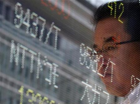 A man is reflected on an electronic monitor displaying share prices outside a brokerage in Tokyo July 9, 2012. REUTERS/Issei Kato