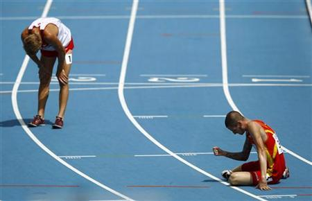 Angel Mullera of Spain (R) sits on the track near Matthew Hughes of Canada after their men's 3,000 metres steeplechase heat at the IAAF World Championships in Daegu August 29, 2011. REUTERS/David Gray