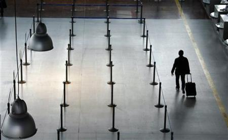 A passengers walks past empty counters at Nice International airport after several flights were cancelled due to a strike by air traffic controllers in Nice, southeastern France, February 23, 2010. REUTERS/Eric Gaillard