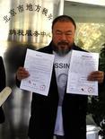 Artista dissidente da China, Ai Weiwei, mostra comprovantes do acordo de obrigações fiscais que firmou com o governo chinês em novembro de 2011. O artista pagou, na época, o equivalente a 8,45 milhões de iuans (1,3 milhões de dólares), a fim de arquivar as acusações de evasão fiscal. Nesta sexta-feira, um tribunal chinês manteve a multa de 2,4 milhões de dólares por evasão tributária imposta a Weiwei, que foi proibido de assistir à audiência. Críticos acusam o governo chinês de usar esse processo para calar o polêmico artista. 16/11/2011 REUTERS/David Gray
