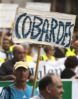 A protester carries a sign that reads, ''Cowards'' during a demonstration against government austerity measures in central Valencia, July 19, 2012. REUTERS/Heino Kalis