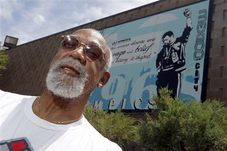 John Carlos, participant of the 1968 Olympics, stands in front of a mural made by students on the campus, at Palm Springs High School, where he is a teacher and counsellor in Palm Springs, California July 11, 2012. Picture taken July 11, 2012. REUTERS/Alex Gallardo