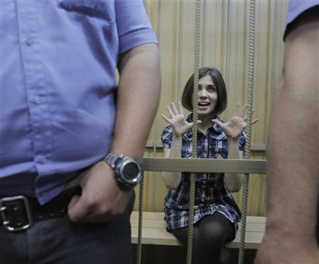 Nadezhda Tolokonnikova, a member of female punk band, ''Pussy Riot'', gestures as she sits behind bars during a court hearing in Moscow June 20, 2012. REUTERS/Denis Sinyakov