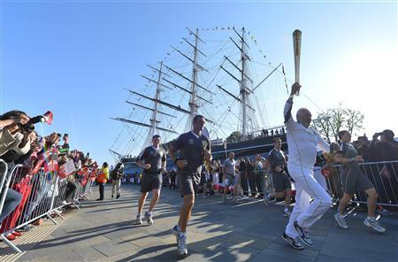 British around-the-world sailor Sir Robin Knox-Johnson carries the Olympic Torch around the restored Cutty Sark boat at Greenwich in London July 21, 2012. REUTERS/Toby Melville