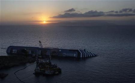 The Costa Concordia cruise ship lies on its side, half-submerged during sunrise at Giglio Island July 14, 2012. REUTERS/Remo Casilli