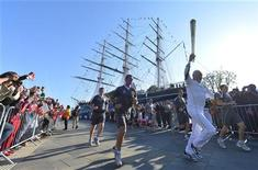 Robin Knox-Johnson carrega a tocha olímpica no barco restaurado Cutty Sark em Greenwich, Londres. A tocha olímpica começou a percorrer seu trecho final no bairro londrino de Greenwich neste sábado, uma jornada que as autoridades esperam que ajude a dissipar a nuvem de desânimo e cinismo que paira sobre a Olimpíada. 21/07/2012 REUTERS/Toby Melville