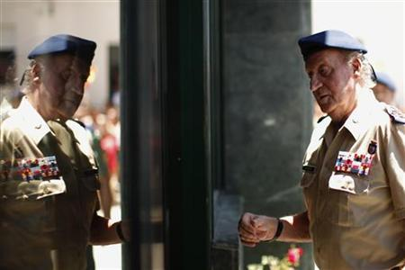 Spain's King Juan Carlos is reflected in a window as he arrives to visit the headquarters of the Spanish Civil Guard at Algeciras, southern Spain, June 20, 2012. REUTERS/Jon Nazca