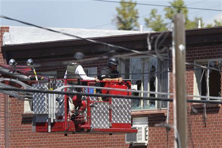 Law enforcement officers use a fire truck lift to inspect the apartment where suspect James Eagan Holmes lived in Aurora, Colorado July 21, 2012. Police probing a Colorado shooting rampage prepared on Saturday to send in a robot to detonate what they called a sophisticated booby-trap in the apartment of Holmes, 24, accused of killing 12 people at a screening of the new ''Batman'' film. REUTERS/Joshua Lott