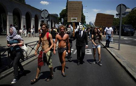 Demonstrators wearing Guy Fawkes masks march outside the Spanish Labour Ministry during an unemployment protest in Madrid July 21, 2012. REUTERS/Javier Barbancho