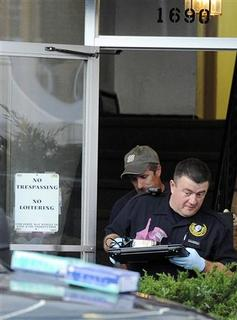 Investigators carry out a computer hard drive and other evidence from the apartment of James Holmes, the suspect who opened fire in a movie theater in Aurora, Colorado July 21, 2012. REUTERS/Jeremy Papasso