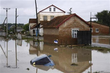 A car lies submerged in a flooded street in the village of Novoukrainsk, near the southern Russian town of Krymsk, July 7, 2012. REUTERS/VladimirAnosov