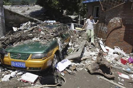 A resident walks past debris and a taxi damaged by a flood after heavy rainfalls hit Mentougou District in Beijing July 22, 2012. REUTERS/Stringer