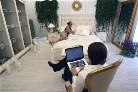 A man sits with his computer at a furniture and chinaware booth during the Summer Fair in Moscow July 4, 2010. REUTERS/Sergei Karpukhin/Files